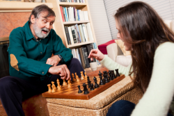 elderly man and her daughter playing chess