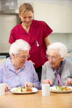 nurse assisting elder women to eat
